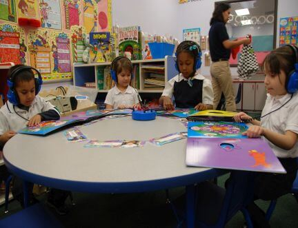 KWAS preschool children sitting at a table reading