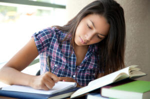 Girl doing homework, writing in a notebook with books and reading